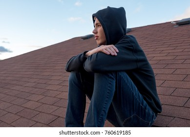 Depressed teen boy sitting on the roof of a house during sunset.