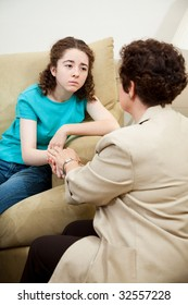 Depressed teen girl gets counseling and comfort from a caring therapist.