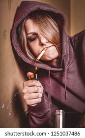 Depressed Teen girl with hangover holding alcohol and fire a cigarette.