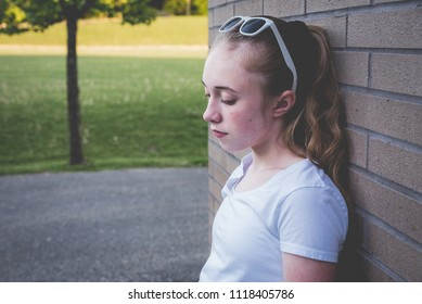 Depressed teen girl standing next to a brick/school wall during sunset next to a sports field.