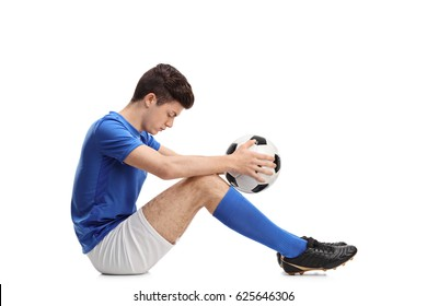 Depressed teenage football player sitting on the floor isolated on white background