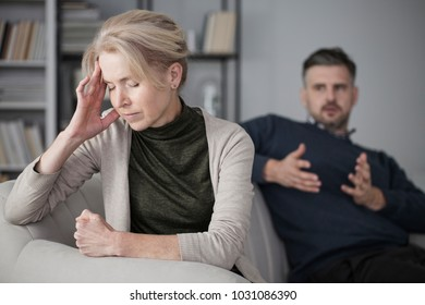 Depressed and tired wife with a headache in the middle of a conflict with a jealous husband