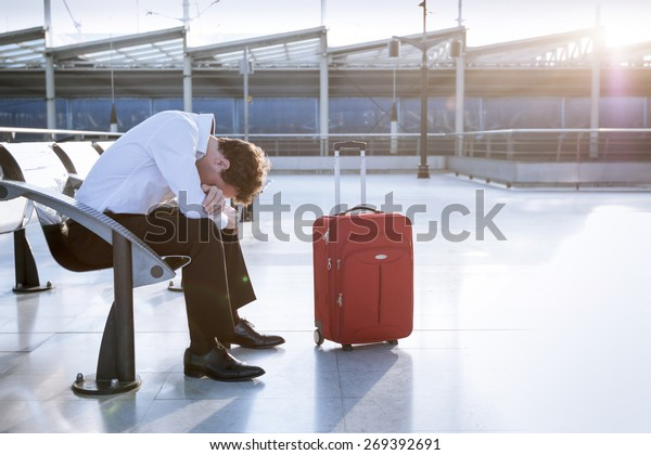 Depressed traveler waiting at airport after flights delays and cancellations