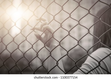 Depressed, trouble, help and chance. Hopeless women raise hand on chain-link fence ask for help