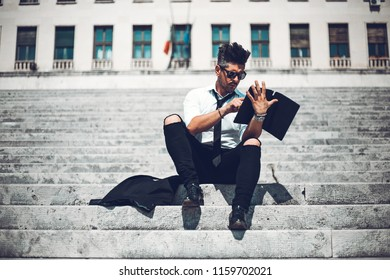 Depressed unsuccessful businessman feels terrible headache, hands shocked by bankruptcy stock downfall sitting on stone stairs. Stressed tired man feels despair lost money online or got problem debt.