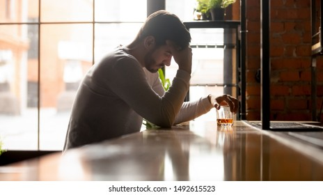 Depressed upset young man drinker addicted to alcohol drink whiskey alone in bar on daytime, sad stressed alcoholic abuse guy get drunk sit at counter with glass feel lonely desperate about addiction