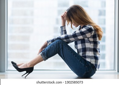 Depressed vulnerable young woman in trouble sitting on floor alone feeling lost upset and lonely, sad female victim feeling bad hurt or tired having drama or psychological problems, regrets mistake
