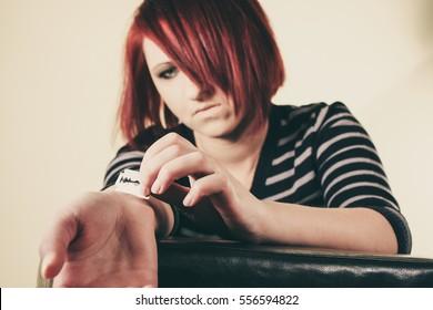 Depressed woman cutting her wrist with razor