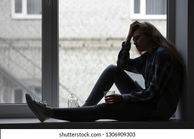 Depressed woman drinking alcohol near window
