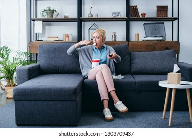 depressed woman eating ice cream while siitng on couch and watching tv at home alone