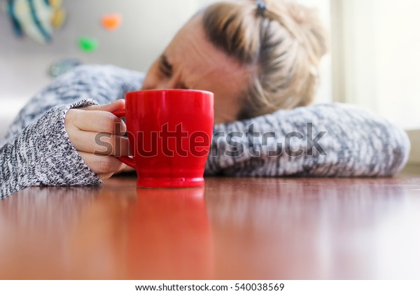Depressed woman laying on a desk with a cup of coffee in hand
