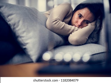 Depressed woman lying on the bed