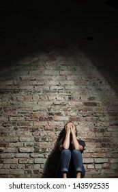 Depressed woman sitting alone against brick wall with light coming from above.