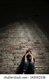 Depressed woman sitting alone against brick wall.