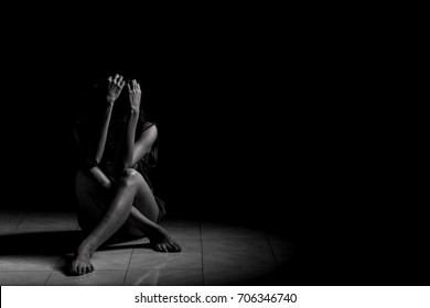 A depressed woman is sitting alone in a dark room.