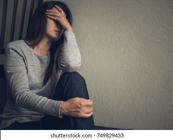 Depressed woman sitting alone in dark room at home. Lonly , sad, emotion concept.