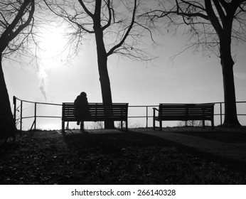 depressed woman sitting alone on a park bench