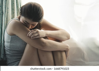 depressed woman sitting in the corner of the room and feeling fear violence from harassment.