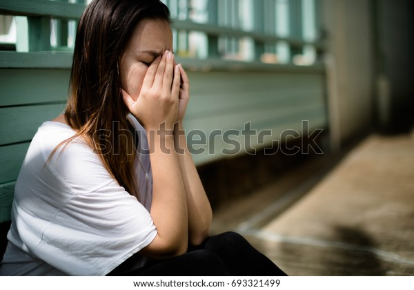 Depressed woman sitting with her hands covering her face overwhelmed with emotion