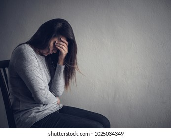 Depressed woman sitting on a chair in dark room at home. Lonly , sad, emotion concept.