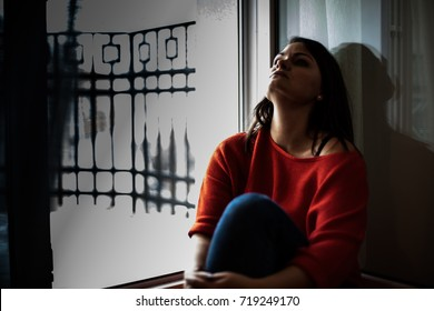Depressed woman sitting on the floor near balcony, looking at rain, feel tired, lonely and unhappy.