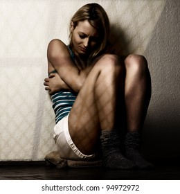 Depressed woman sitting on the floor.