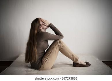 Depressed woman sitting on a mattress