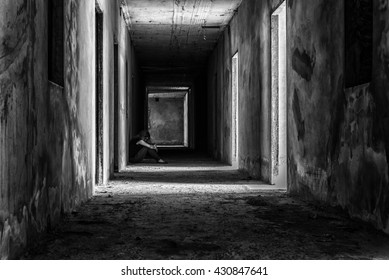 depressed woman sitting on walkway in creepy abandoned building, darkness concept