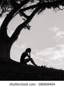 Depressed woman sitting under the tree outdoors.