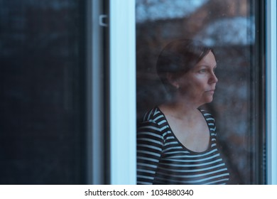 Depressed woman standing by the window and looking outside at snow falling in cold winter afternoon, teal and orange toned image