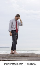Depressed or worried businessman standing barefoot at the sea