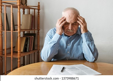 Depressed worried senior man looking at a form on the table in front of him awaiting his signature resting his head in his hands with a morose expression