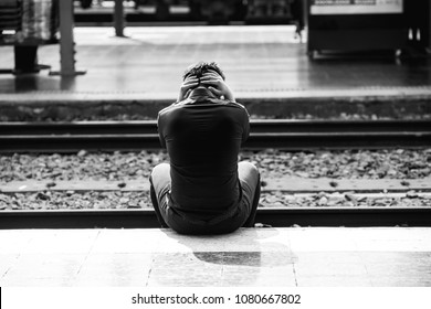 Depressed young asian business man holding his head in hand at train station, unemployed,dismiss