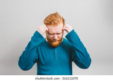 Depressed young business man holding his head