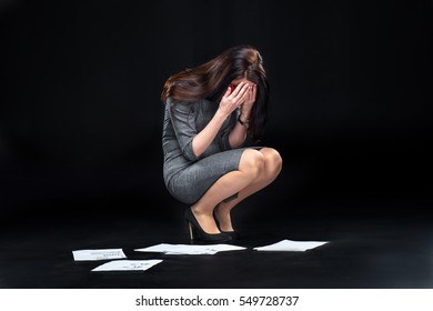 Depressed young businesswoman crying over dropped documents isolated on black