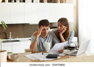 Depressed young Caucasian couple calculating family budget in kitchen, trying to find a way to make both ends meet, having stressed and frustrated looks: caring wife embracing her unhappy husband