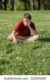 Depressed young Caucasian teen sitting on grass