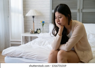 Depressed young girl in casual wear sit on bed in cozy bedroom. thoughtful asian woman resting at home put hand on chin thinking problems. worried lady feeling sad indoors on weekend looks frustrated