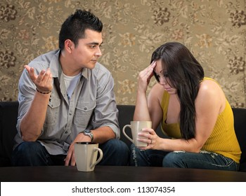 Depressed young Hispanic woman in conversation with man