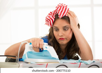 Depressed young housewife ironing clothes