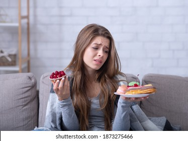 Depressed young lady having eating disorder, comforting herself with sweets on sofa at home. Unhappy millennial woman coping with negative emotions through food, suffering from bulimia