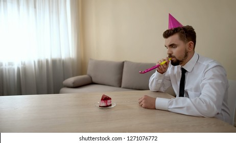 Depressed young male in party hat celebrating birthday alone, depression crisis