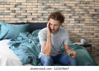 Depressed young man drinking alcohol at home