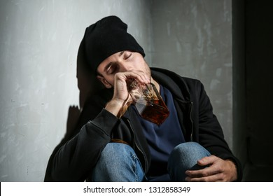 Depressed young man drinking whiskey in dark room. Alcoholism concept