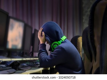 Depressed young man at internet cafe scene,Conceptual game addiction, social problem.