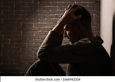 Depressed young man near grey wall