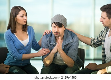 Depressed young man is sitting at the chair while two other people are comforting his.