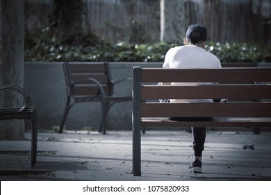 Depressed  young man sitting on a bench in the park feeling loneliness. Empty copy space for Editor's text.