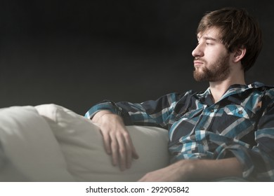 Depressed young man is sitting on couch
