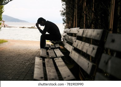Depressed young man sitting on the bench in tunnel.